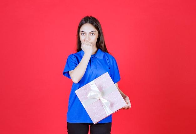 Donna che tiene una scatola regalo rosa legata con un nastro bianco e sembra confusa o ha una buona idea.