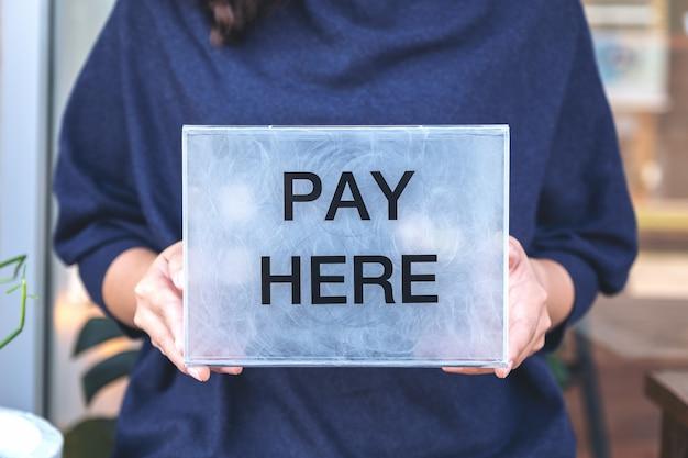 Una donna che tiene una scatola di pagamento in plastica