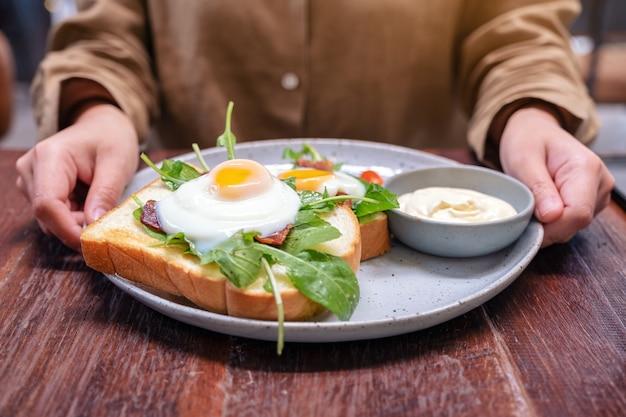 Una donna che tiene un piatto di panino per la colazione con uova, pancetta e panna acida sul tavolo di legno
