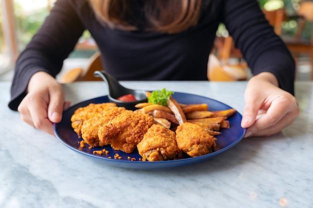 Donna che tiene un piatto di pollo fritto e patatine fritte in ristorante