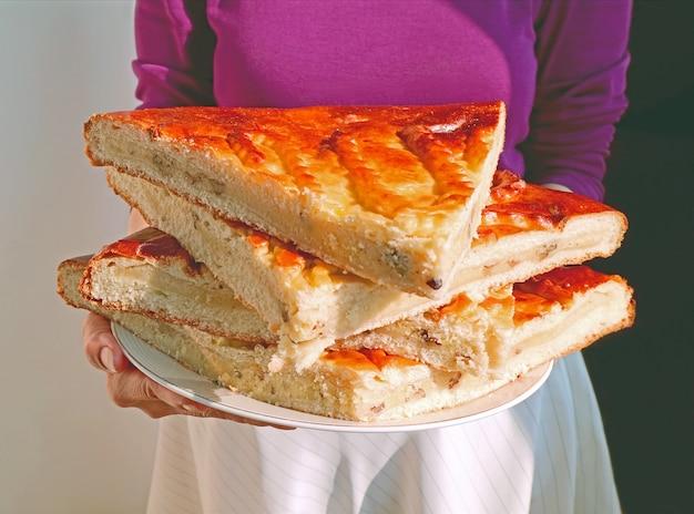 Donna che tiene un piatto di fette di pane tradizionale armeno pila chiamato gata