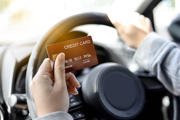 Una donna con in mano una carta di credito rossa, è in macchina, smette di fare il pieno alla stazione di servizio e di pagare con una carta di credito rossa, stava tornando a casa dopo essere andata al lavoro. concetto di carta di credito.