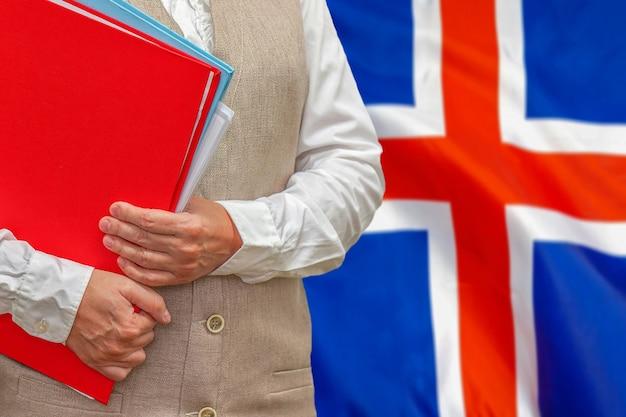 Donna che mantiene la cartella rossa con la bandiera dell'islanda dietro