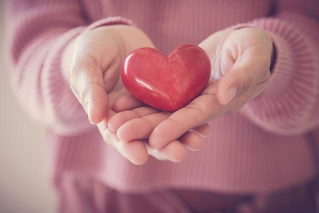 Donna che tiene cuore rosso, assicurazione sanitaria, concetto di donazione, giornata mondiale della salute mentale, giornata mondiale del cuore
