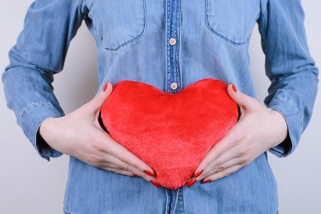 Donna che mantiene cuore rosso vicino all'addome