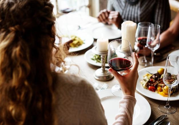 Donna che tiene il bicchiere di vino rosso in un ristorante di classe