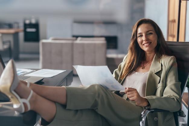 Donna che tiene un foglio di carta, lavorando a casa con i piedi sulla sua scrivania.