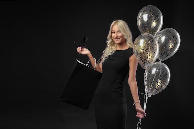 Donna che mantiene una borsa della spesa su uno sfondo nero. celebra le vendite nei negozi. venerdì nero
