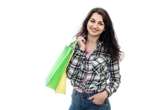 Donna che mantiene i sacchetti della spesa isolati sulla parete bianca