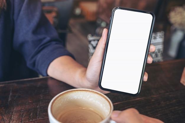 Una donna che tiene e che mostra il telefono cellulare nero con schermo vuoto a qualcuno sul tavolo nella caffetteria