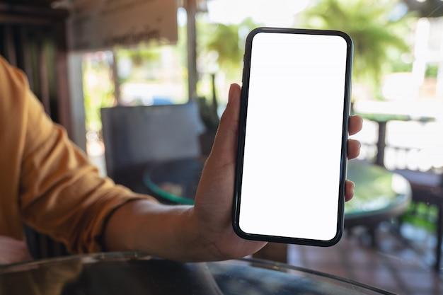 Una donna che tiene e mostrando il telefono cellulare nero con lo schermo del desktop bianco vuoto