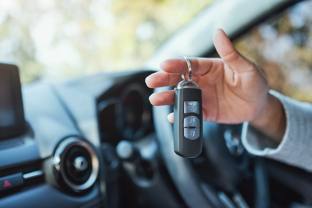 Una donna che tiene e mostra la chiave della macchina mentre è seduta in macchina