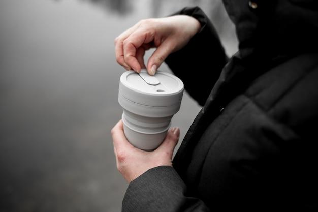 Donna che tiene una tazza pieghevole in silicone, bicchiere da caffè riutilizzabile.