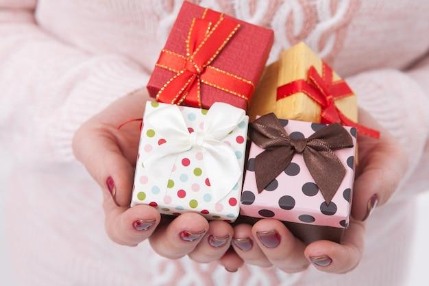 Donna che tiene piccoli contenitori di regalo di natale