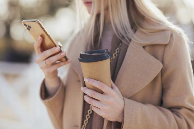Donna che tiene smartphone e bere caffè