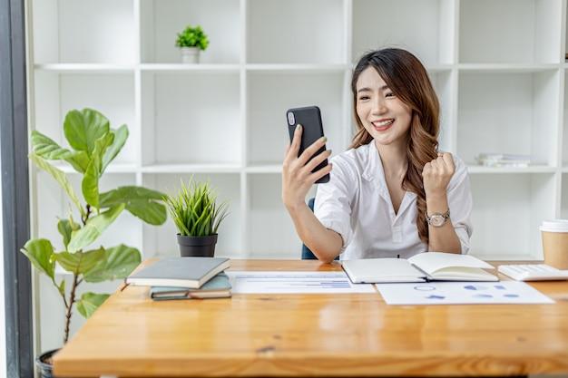 Donna in possesso di uno smartphone e gesticolando, donna d'affari asiatica che mostra gioia dopo aver visto i crescenti guadagni dell'azienda nell'ultimo mese, gestisce la crescita. concetto di amministrazione aziendale.