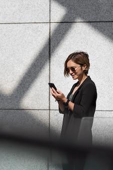 Donna con smartphone colpo medio