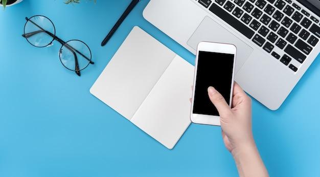 Donna che tiene uno smartphone sulla scrivania in ufficio
