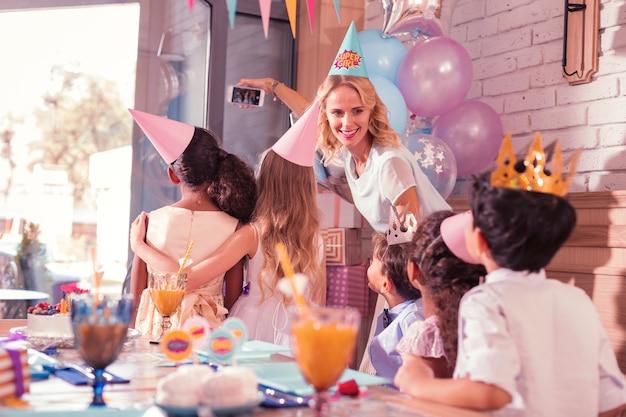 Donna che tiene smartphone e scattare foto con i bambini alla festa