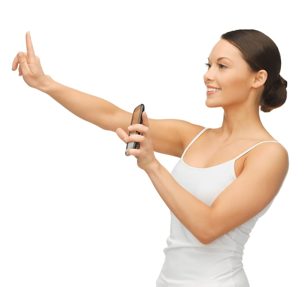 Donna che tiene in mano uno smartphone e lavora con qualcosa di immaginario