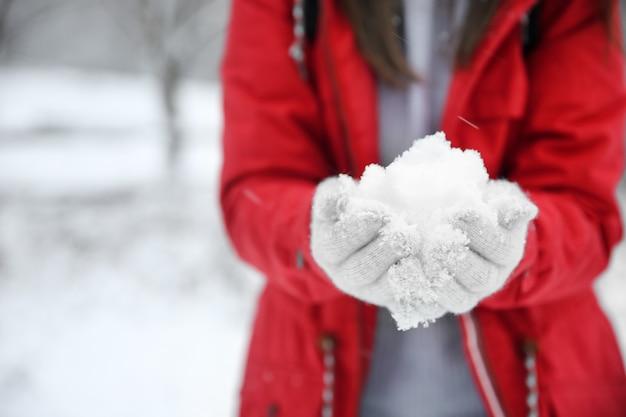 Donna che tiene la neve nelle mani il giorno d'inverno, primo piano