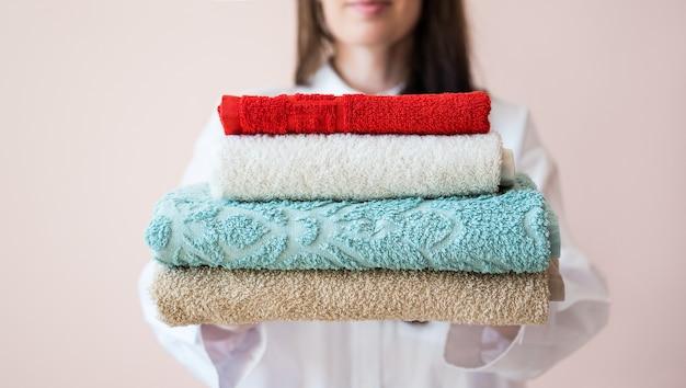Donna che tiene una pila di asciugamani piegati servizio di pulizia