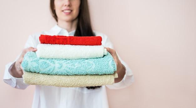 Donna che tiene una pila di asciugamani piegati
