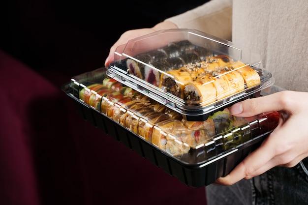 Donna che tiene la scatola di sushi su sfondo nero
