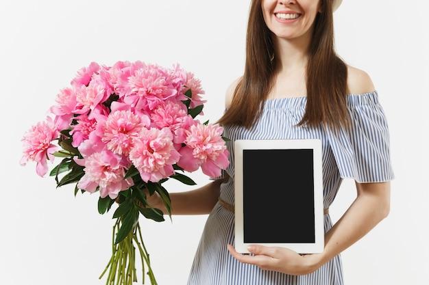 Donna che tiene il computer tablet con schermo vuoto vuoto per copiare lo spazio, bouquet di bellissimi fiori di peonie rosa isolati su sfondo bianco. concetto di acquisto online di consegna di affari. area pubblicitaria