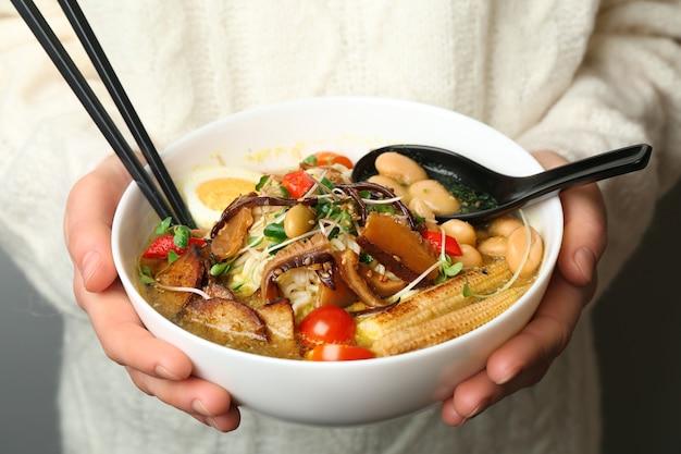 Donna che tiene una gustosa zuppa cinese, primo piano