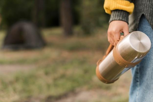 Donna che mantiene thermos durante il campeggio con copia spazio