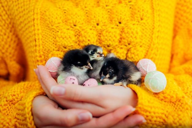 Donna che tiene in mano tre pulcini neri circondati con le uova di pasqua.