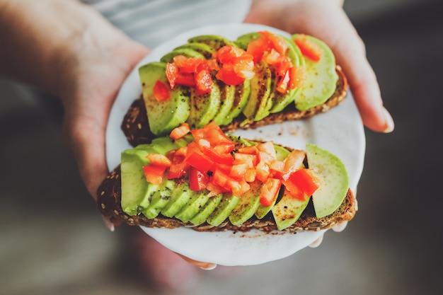 Donna che tiene i toast con avocado e pomodori sul piatto.