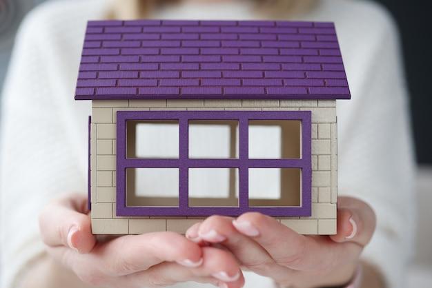Donna che mantiene casa in legno giocattolo nelle sue mani