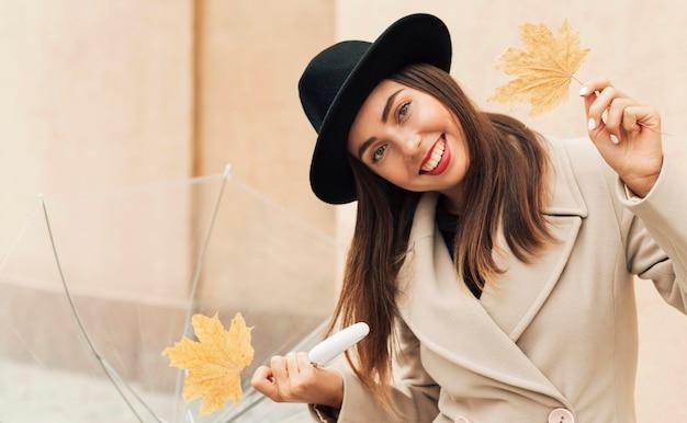 Donna che tiene un ombrello e foglie trasparenti