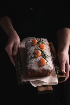 Vassoio della holding della donna con la torta di natale