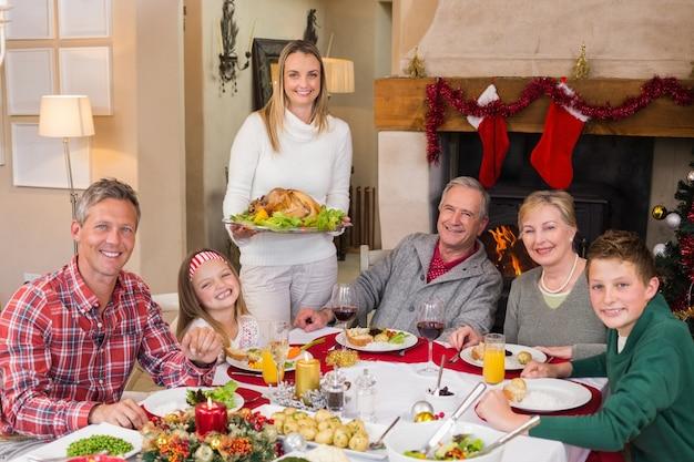 Arrosto di tacchino della holding della donna con la famiglia al tavolo da pranzo