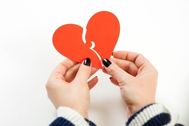 Donna che tiene due parti di cuore di carta. buon san valentino. essere innamorato.