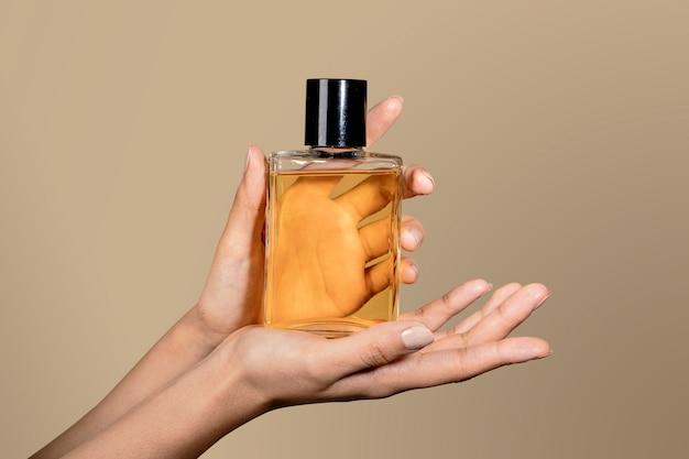 Donna che tiene una bottiglia di vetro di profumo senza etichetta