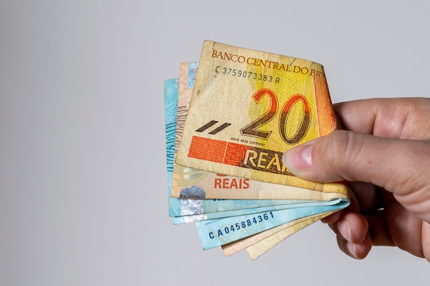 Donna che tiene banconote in denaro brasiliano usate