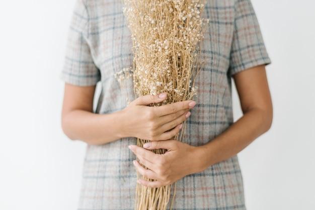Donna che tiene in mano un abito scozzese con in mano fiori secchi