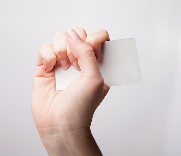 Donna che tiene un biglietto da visita bianco in mano, da vicino