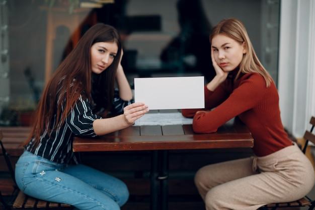 Donna con carta bianca in mano. due donne che parlano a tavola in street cafe. foglio modello vuoto bianco con spazio vuoto.