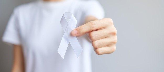Donna che tiene il nastro bianco per il mese di sensibilizzazione sul cancro al polmone di novembre, la democrazia e la giornata internazionale della pace. concetto di assistenza sanitaria