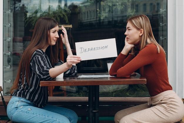 Donna che mantiene il foglio bianco di carta con etichetta parola depressione in mano. due donne che parlano in un caffè di strada. concetto di depressione nascosta