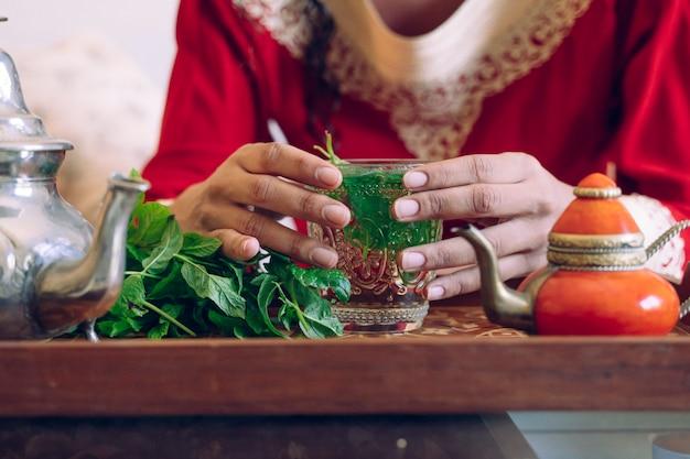 Donna che tiene con il tè arabo verde delle mani