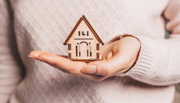 Donna che tiene una casa di legno con le mani, assicurazione su una superficie rosa chiaro. dolce casa