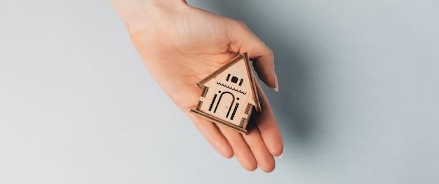 Donna che tiene una casa in legno con le sue mani con il sole su uno sfondo azzurro. dolce casa