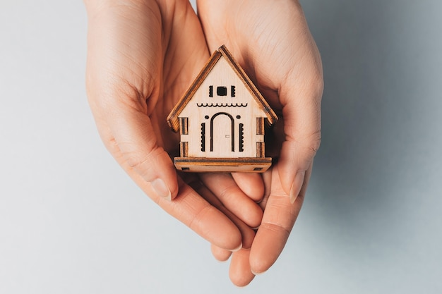Donna che tiene una casa in legno con le mani con il sole su uno spazio azzurro
