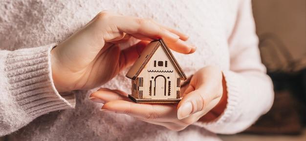 Donna che tiene una casa in legno con le sue mani con il sole su uno sfondo rosa chiaro. dolce casa